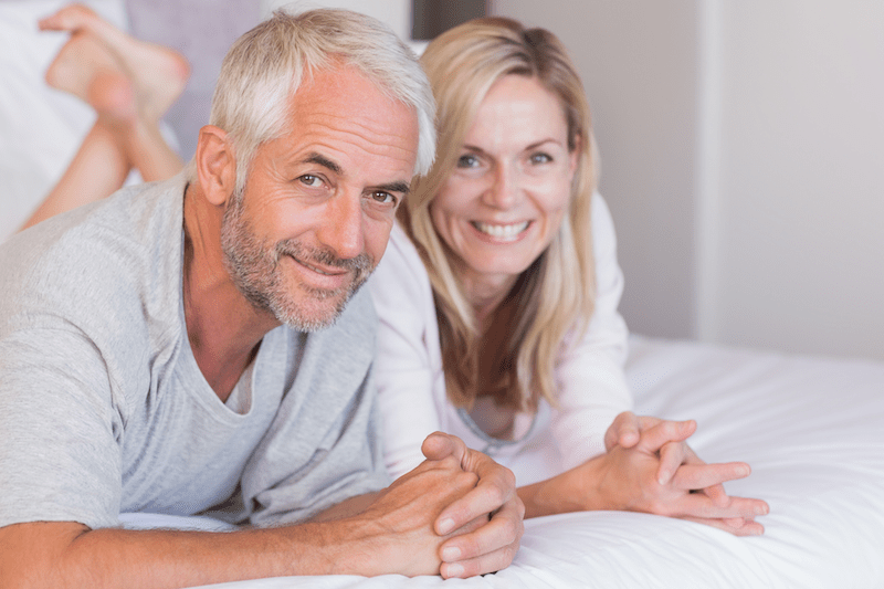 smiling man and woman in bed